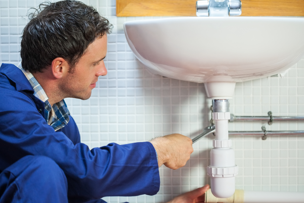 Handsome happy plumber repairing sink in public bathroom